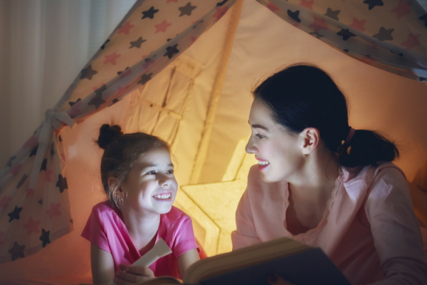 Mor og datter i telt med lommelygte